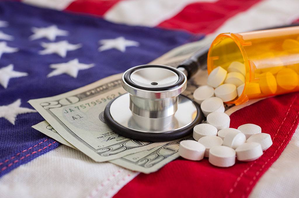 Stethoscope, $20 bills and a prescription bottle with white pills fallout out placed on top of US flag