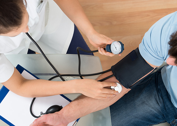 Overhead view of medical assistant taking a man's blood pressure