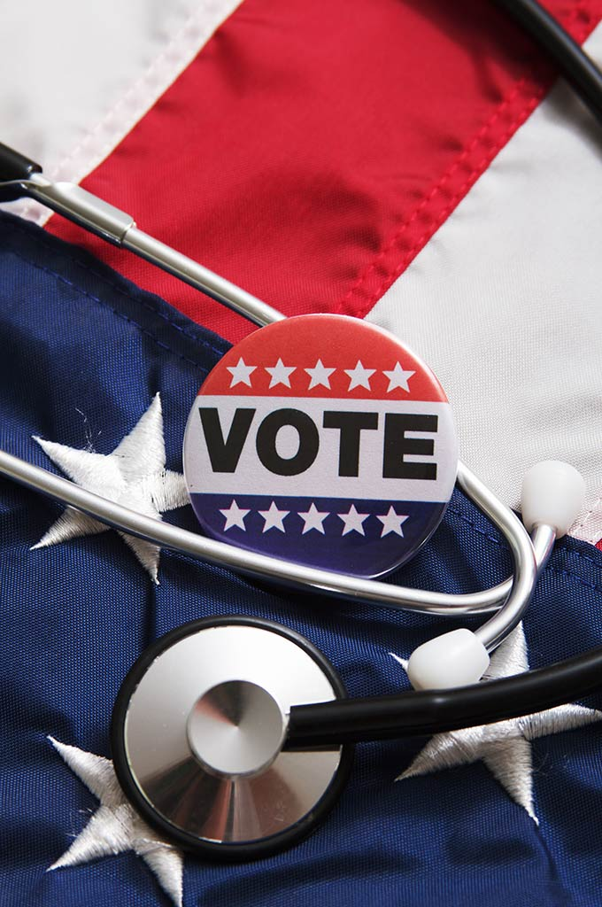 """Vote"" button and stethoscope on top of US flag"