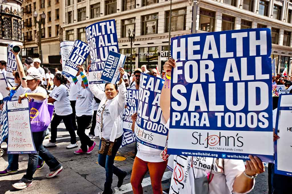 "Marchers on the street holding up signs that say, ""Health for all"""