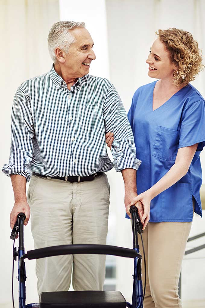 Physical therapist working with a senior man on using his walker