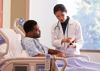 Patient in hospital bed reviews his test results with the doctor on the doctor's tablet