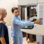 Female radiologist setting up mammogram machine