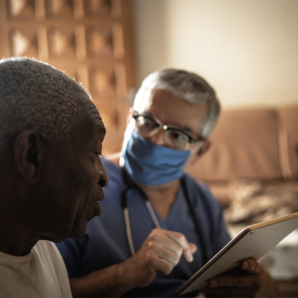 Health visitor and a senior man during home visit - using digital tablet