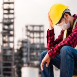 construction worker with hard hat and protective mask sits dejectedly. The building framework is out of focus in the background.